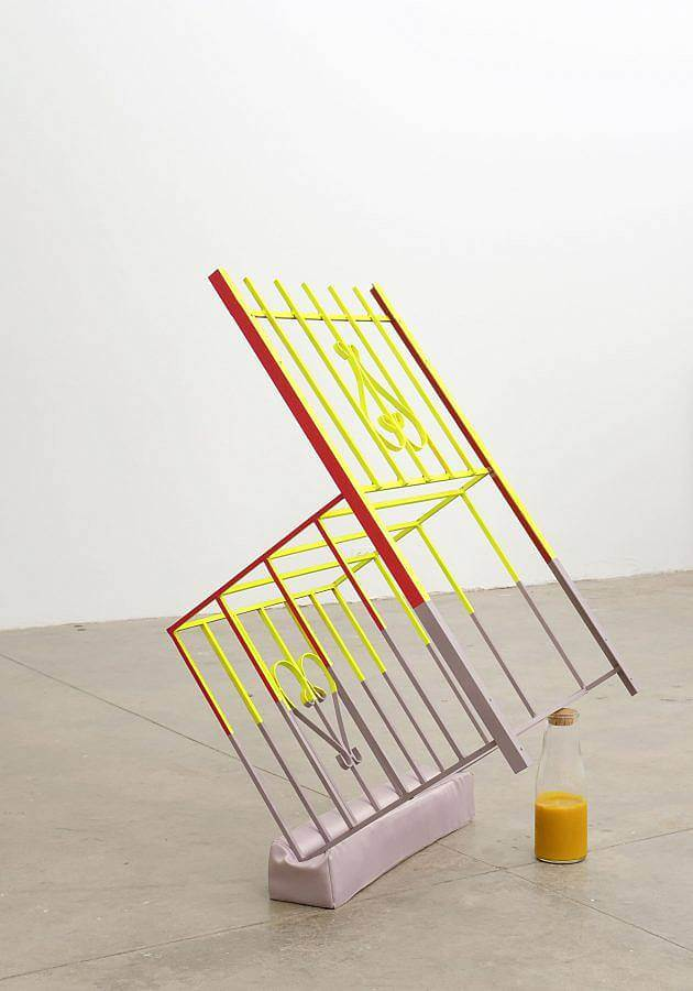 Image Description: This is a chair made of wrought iron fencing with two heart symbols. The chair is leaning forwards, balanced on a light purple satin rectangular pillow and a half filled bottle of orange juice. The chair is painted red, light green, and light purple.