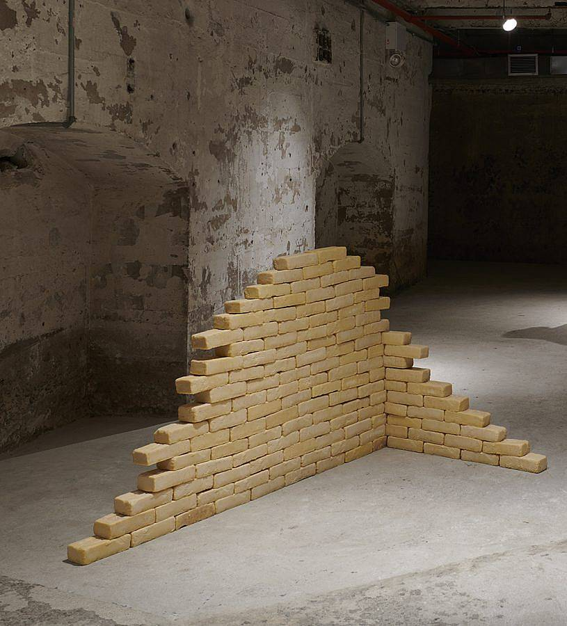 Image Description: There are a large collection of bricks cast in tan cocoa butter. They are arranged in a corner formation with one wall higher than the other.