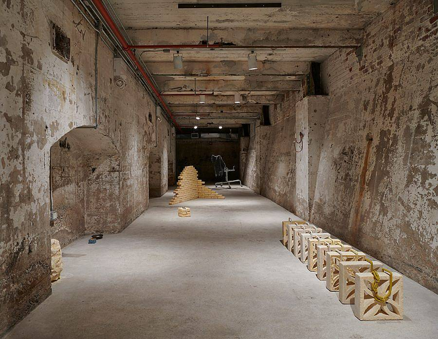 Image Description: This is an installation in a large basement hallway. There is a set of tan breeze blocks casted in cocoa butter lined up with steel rebar along the top. In the distanced is a formation of cocoa butter bricks arranged in a corner formation.