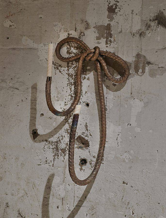 Image Description: There is a loose bow made of steel rebar mounted on the wall. The ends of the rebar are turned upwards and there are white candles mounted on the ends.