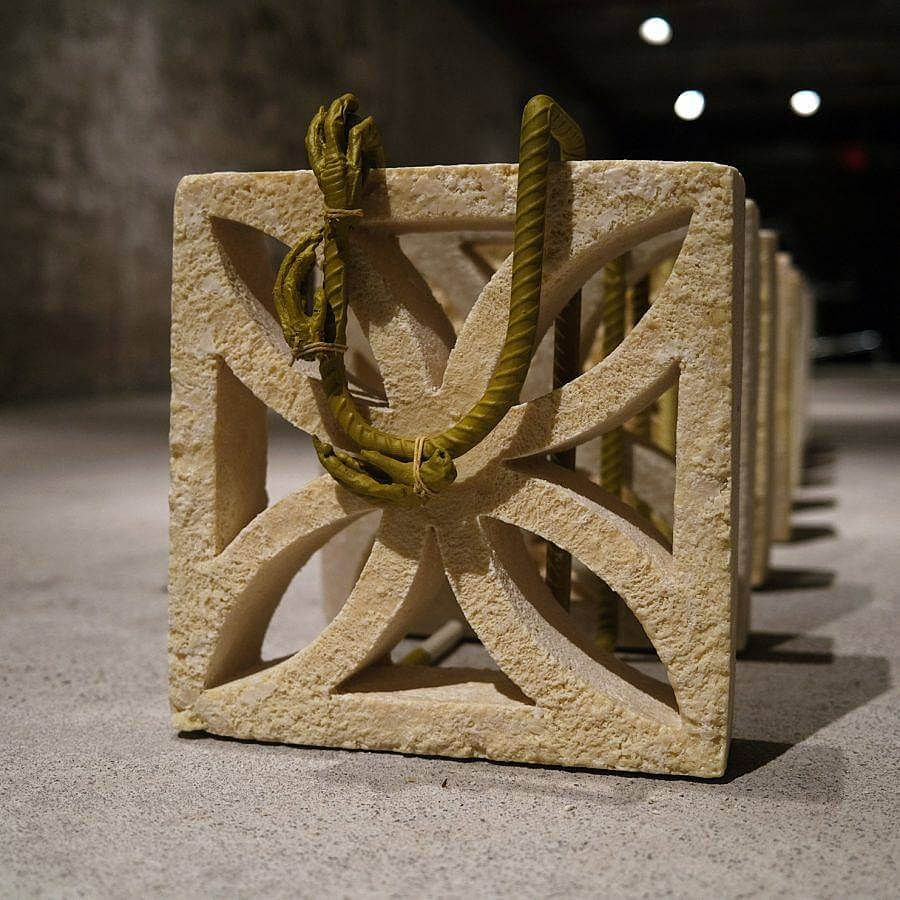 """Image Description: This is a square breeze block cast in tan cocoa butter. There is steel rebar in a """"U"""" attached to the top with steel-cast chicken feet tied to it. This breeze block is set up in a long row of others identical to it."""