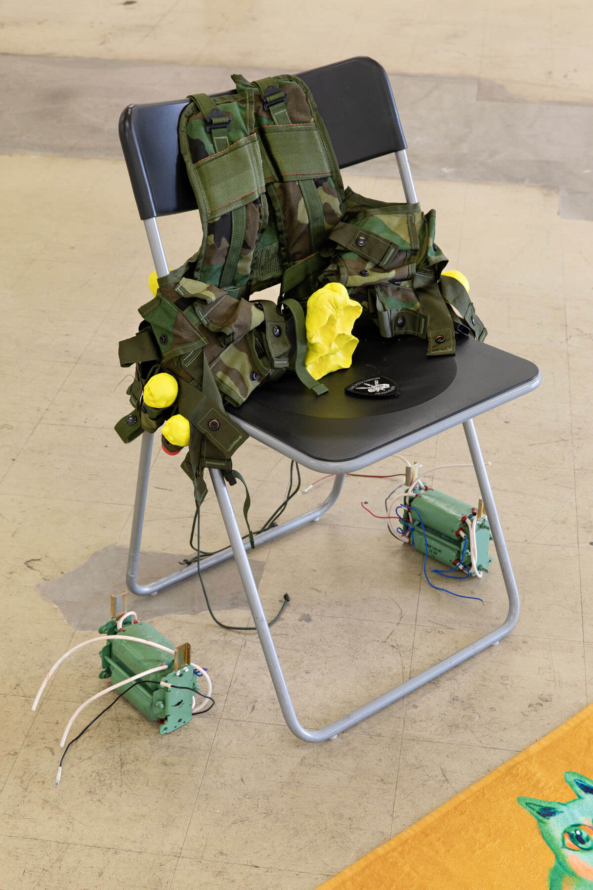 """A picture of a combat vest in a folding chair, from Ville Kallio's 2019 show """"Venmo Combat"""""""