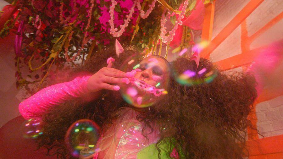 Image Description: This is a still of a person with big curly pigtails blowing bubbles. They have big pink globs on their fingernails and are wearing a pink and green outfit. There is a large plant with streamers in it above them.