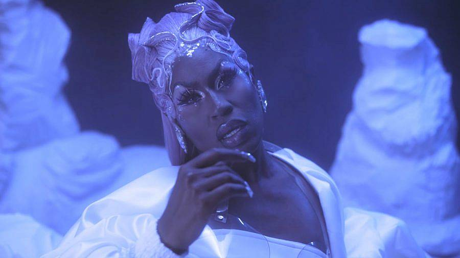 Image Description: This is a still of a drag queen all in blue. The lighting and background is blue with forms resembling icebergs in the background. She has an elaborate updo and long nails.