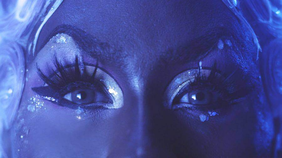 Image Description: This is a still of a drag queen staring straight at the camera. Only their eyes are in shot. They are wearing big fake eyelashes and have large pieces of glitter decorating their eyes.