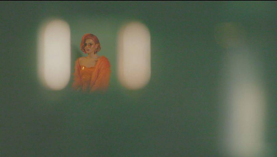 Image Description: This is a still of a drag queen sitting in an empty room. They are dressed all in bright orange with orange hair. All the space around her is blurry.