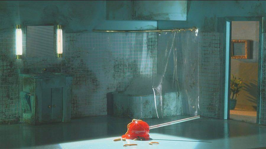 Image Description: This is a still showing a very dirty tiled bathroom. There is a clear shower curtain and a door looking into a hallway with plants. A giant red lollipop is melting in the center of the floor.