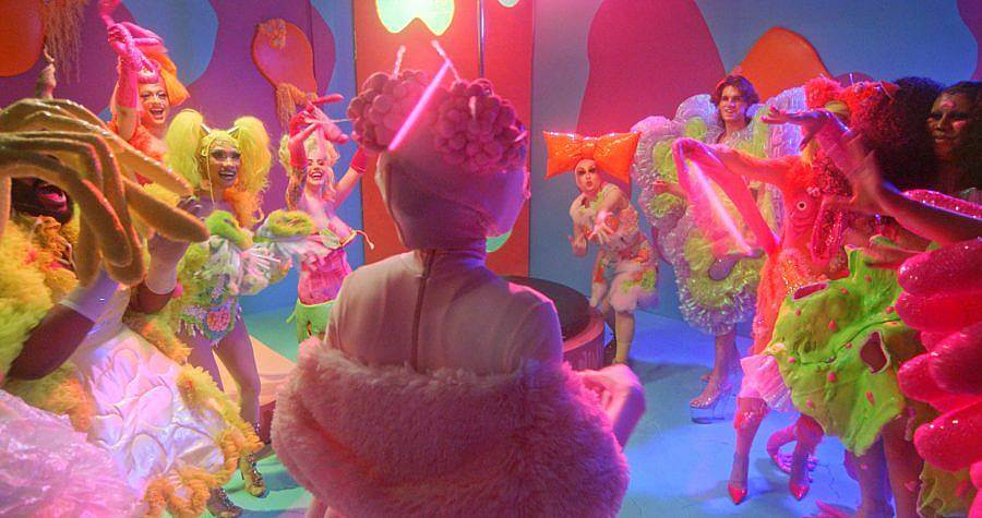 Image Description: This is a still with many people in elaborate colorful costumes with big hairstyles. The set is also multi-colored and a party appears to be happening.